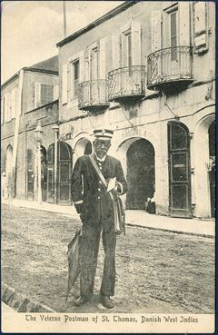 Postcard 'The Veteran Postman of St. Thomas, Danish West Indies'. He is Mr. Joseph Lorand, the longest serving postal service worker in the Danish West Indies and was honored and received the silver cross of Dannebrogsmand.